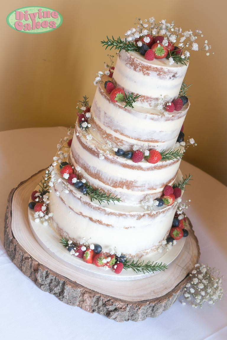 semi naked wedding cake with berries and flowers